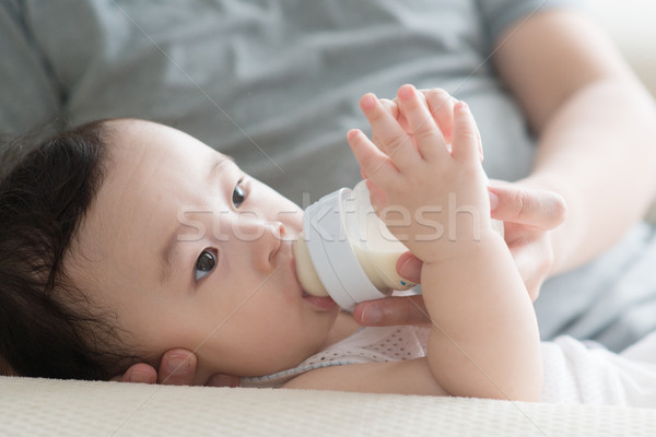 Father bottle feed milk to son. Stock photo © szefei