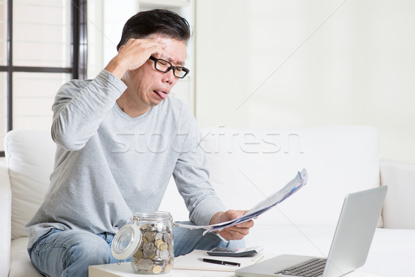Stressed mature Asian man paying bill at home.  Stock photo © szefei
