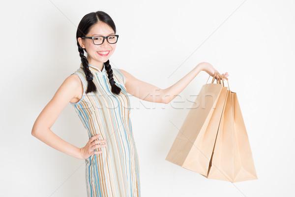 Oriental female holding shopping paper bag Stock photo © szefei