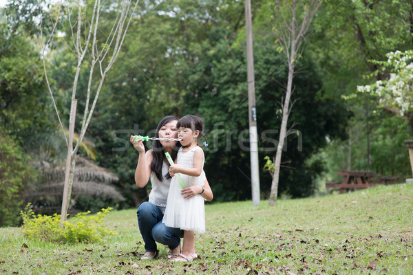 Mother and daughter blowing soap bubbles Stock photo © szefei
