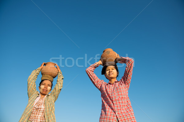 Asian traditional farmers carrying pot on head Stock photo © szefei