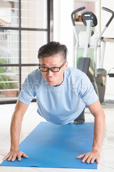 Mature Asian man pushup at gym Stock photo © szefei