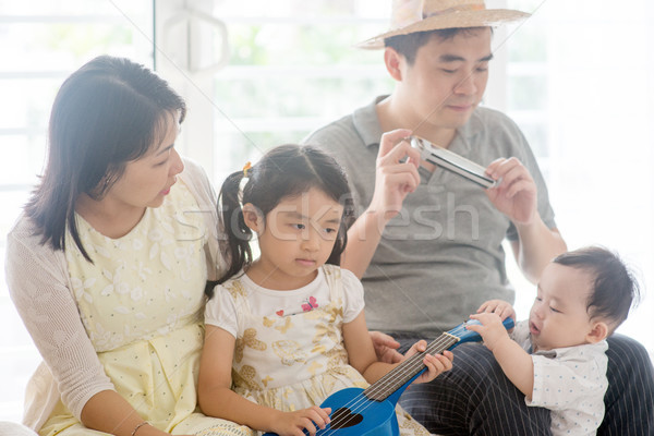 Family playing music instrument at home Stock photo © szefei