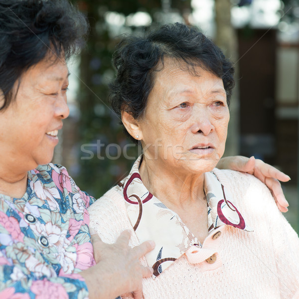 Mature woman consoling her crying old mother Stock photo © szefei