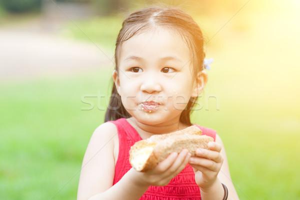 Asian child eating outdoors. Stock photo © szefei