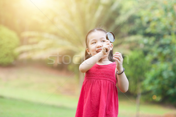 Little girl exploring nature with magnifier glass at outdoors. Stock photo © szefei