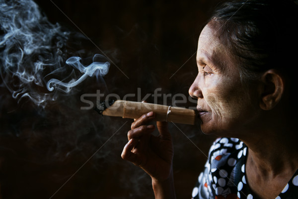 Old wrinkled Asian woman smoking Stock photo © szefei