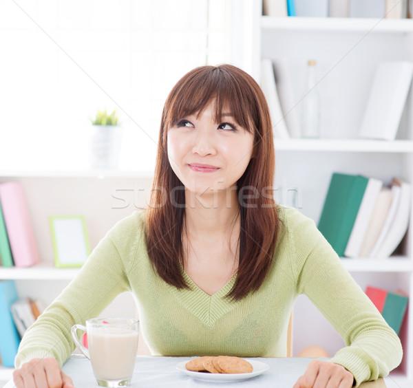 Asian girl eating breakfast and thinking Stock photo © szefei