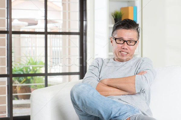 Mature 50s Asian male sitting at home. Stock photo © szefei