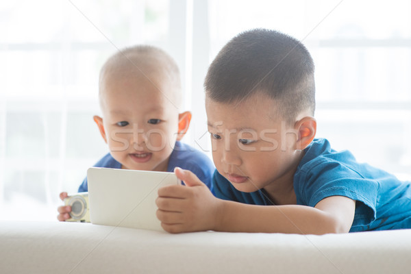 Kids addicted to smart phone. Stock photo © szefei