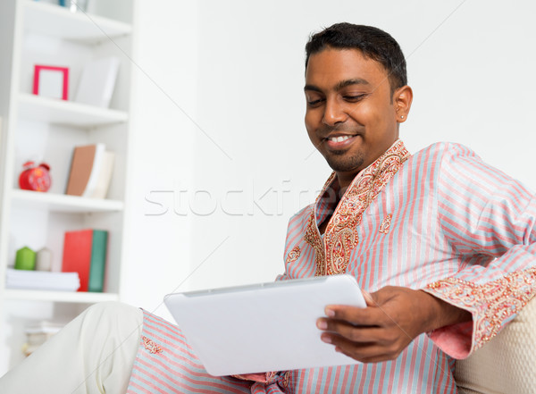 Indian man using digital tablet at home. Stock photo © szefei