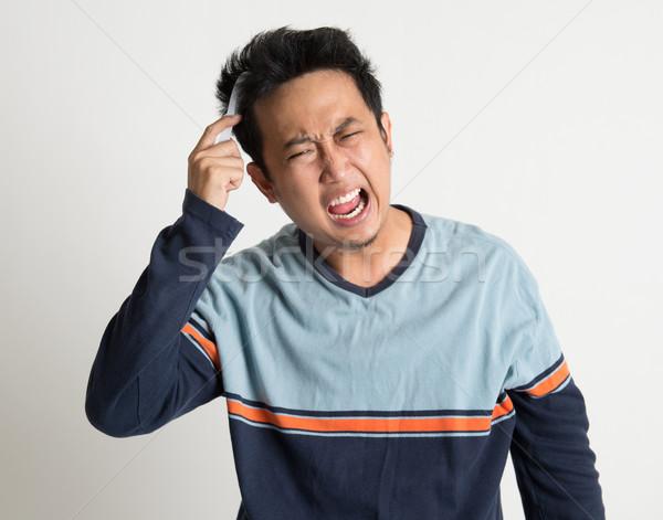 Asian man combing his tangled hair  Stock photo © szefei