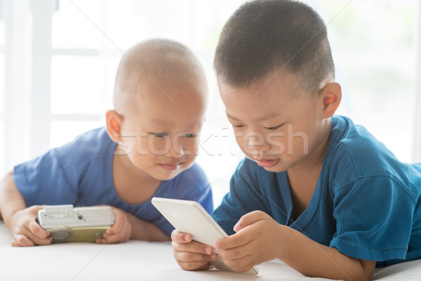 Young children addicted to smart phone. Stock photo © szefei