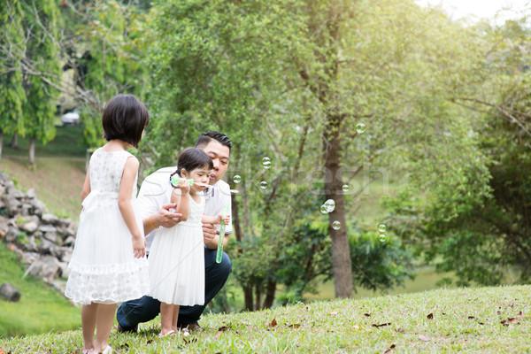 Happy Asian family blowing soap bubbles at park Stock photo © szefei