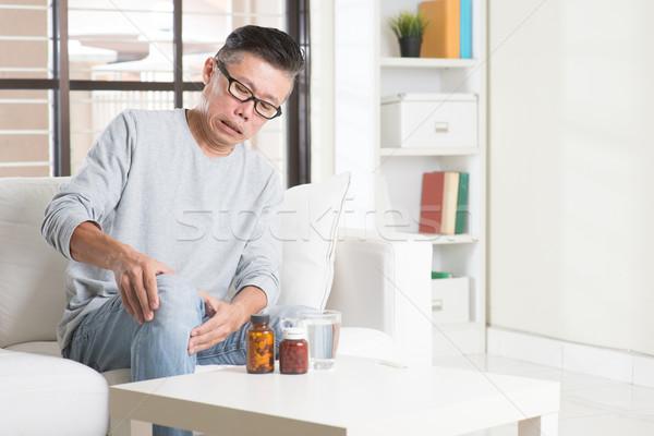 érett ázsiai férfi térd fájdalom portré Stock fotó © szefei