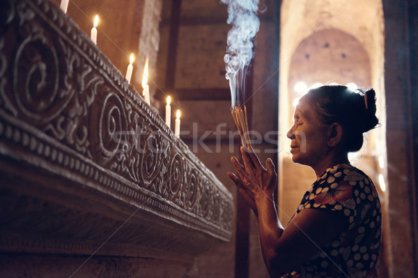 Old wrinkled traditional Asian woman praying with incense sticks inside a temple, low light, Myanmar Stock photo © szefei
