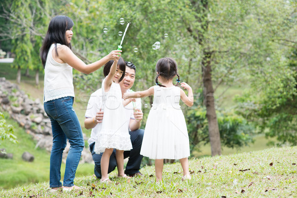 ázsiai család fúj szappanbuborékok park szülők Stock fotó © szefei