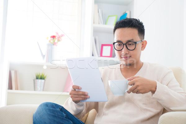 Asian male using computer tablet Stock photo © szefei