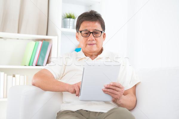 Mature Asian man using tablet pc Stock photo © szefei