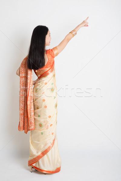 Rear view woman in Indian sari dress pointing Stock photo © szefei
