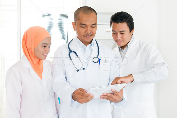 Medical team discussing on tablet pc Stock photo © szefei