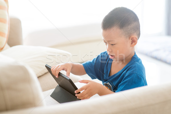 Young child addicted to tablet. Stock photo © szefei