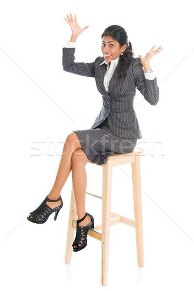 Happy black businesswoman seated on chair. Stock photo © szefei