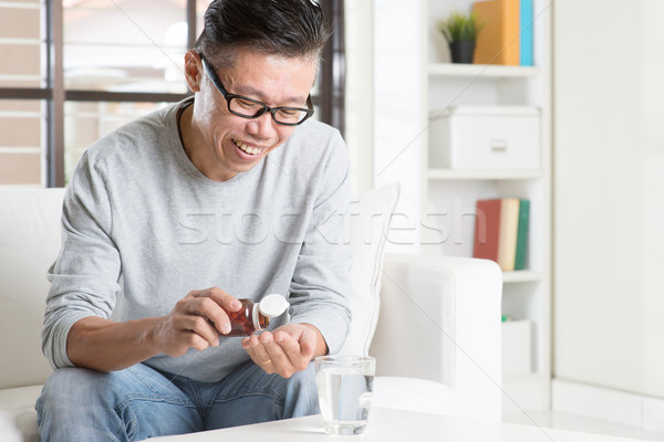 Asian man eating supplement Stock photo © szefei