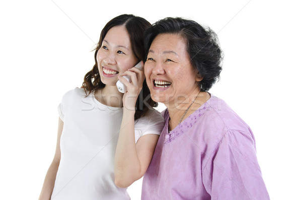 Daughter and mother calling on phone Stock photo © szefei