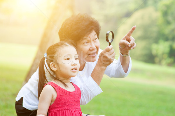 Grandmother and granddaughter exploring outdoor. Stock photo © szefei