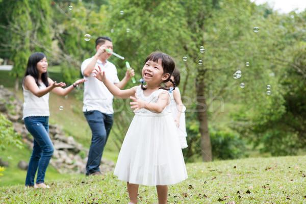 Asian family blowing soap bubbles outdoors Stock photo © szefei