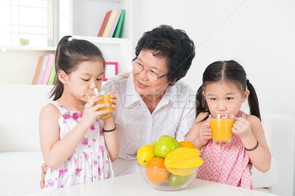 Asya çocuklar içme portakal suyu aile mutlu Stok fotoğraf © szefei