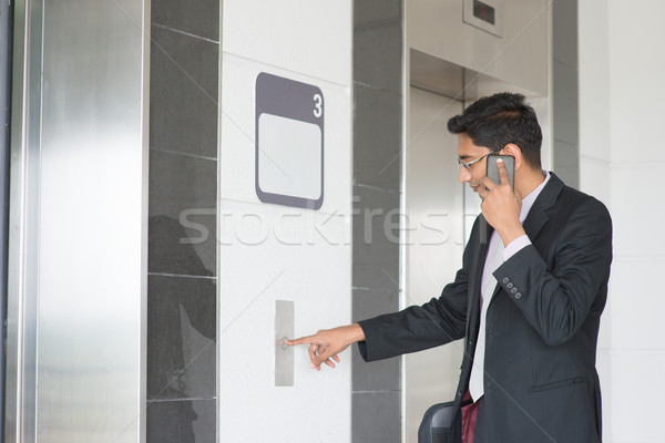 Indian businessman entering elevator Stock photo © szefei