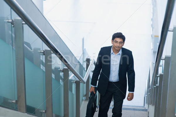 Asian Indian businessman ascending steps Stock photo © szefei
