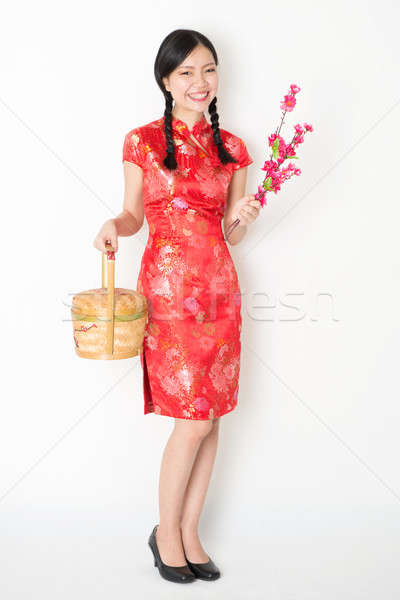 Oriental girl in red qipao holding gift basket Stock photo © szefei