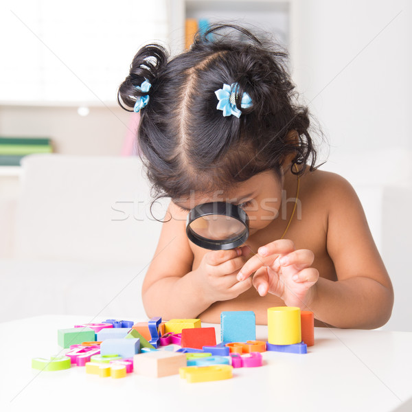 Indian girl zoom into toys through a magnifying glass Stock photo © szefei