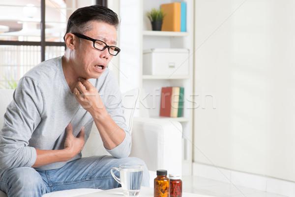 Mature Asian man throat pain Stock photo © szefei