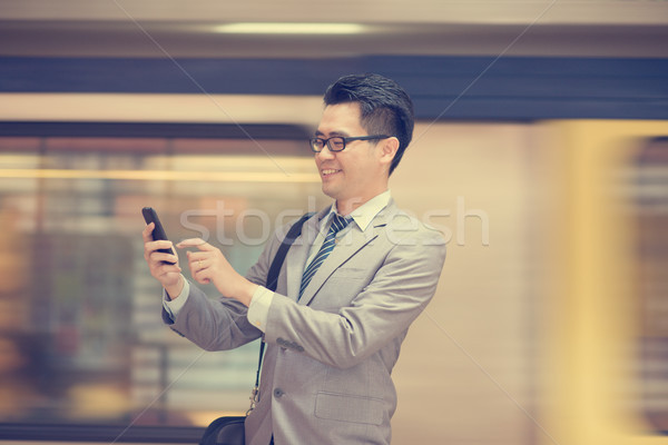 Businessman texting at subway. Stock photo © szefei