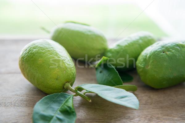 organic green lemons on wood background Stock photo © szefei