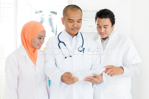 Medical doctors discussing on tablet pc Stock photo © szefei