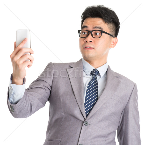 Stock photo: Get shocked while reading on smart phone.