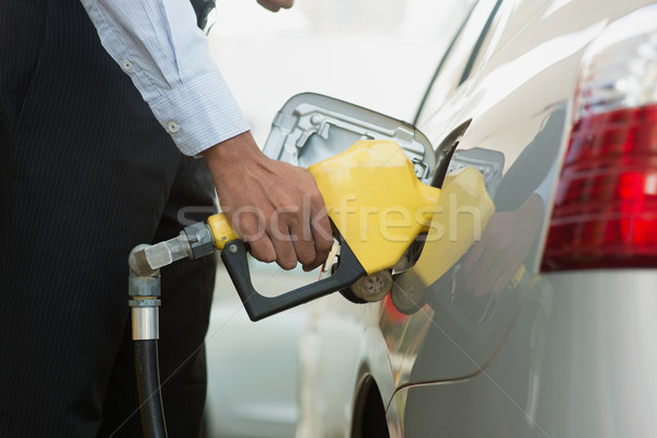 Stock photo: Pumping gasoline fuel at gas station