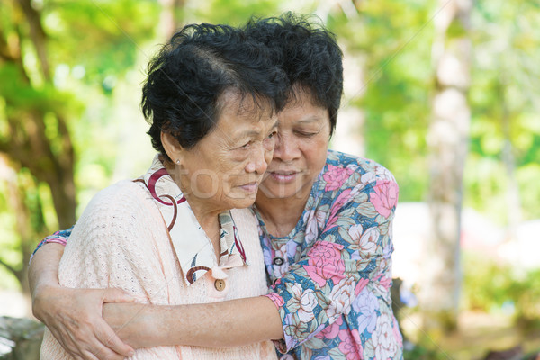 Asian mature woman hugs and consoling her crying old mother Stock photo © szefei