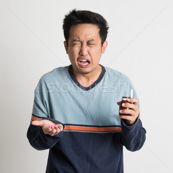 Man holding medicine bottle while sneezing Stock photo © szefei