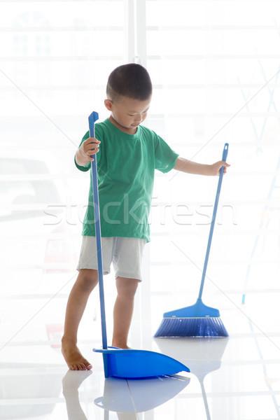 Asian child sweeping floor Stock photo © szefei