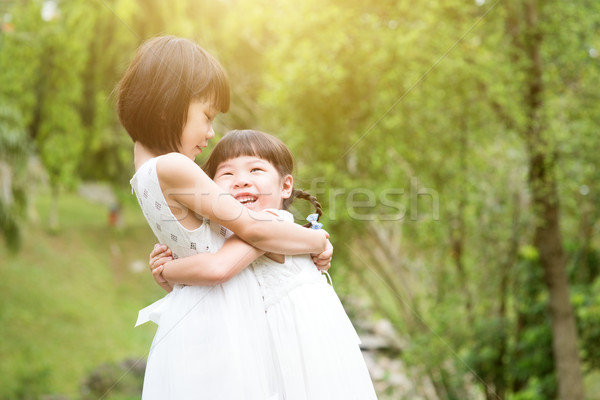 Sisters playing and hugging at outdoors Stock photo © szefei