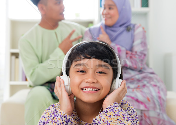 Muslim girl listening to song Stock photo © szefei