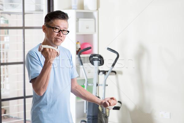 Mature Asian man with dumbbells at gym Stock photo © szefei