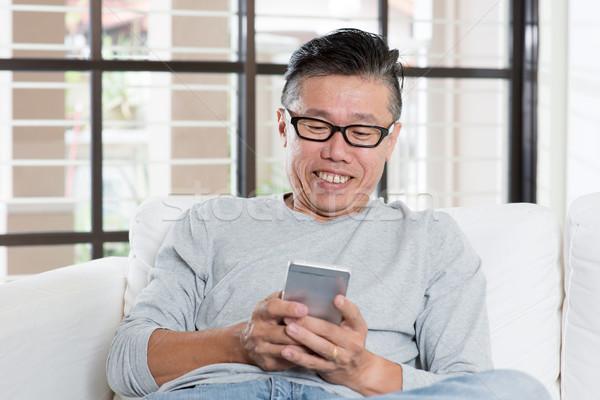 érett ázsiai férfi sms chat okostelefon portré Stock fotó © szefei