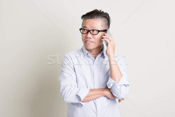 Mature Asian man talking on smartphone Stock photo © szefei